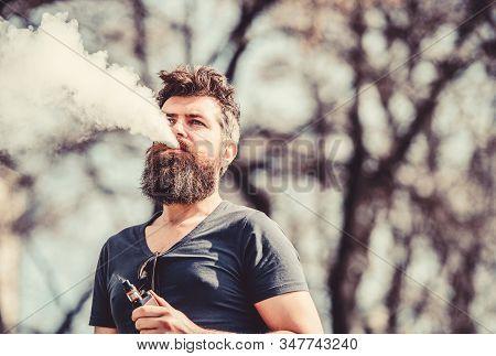 Stress Relief Concept. Bearded Man Smoking Vape. Smoking Electronic Cigarette. Man Long Beard Relaxe