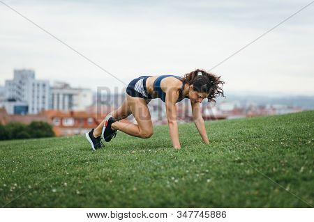 Sporty Young Female Athlete Doing Burpees At City Park For Leg Power Workout.