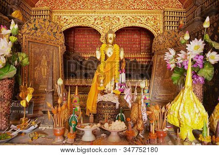 Luang Prabang, Laos - April 16, 2012: Altar With Buddha Statues Decorated With Flowers And Gold In W