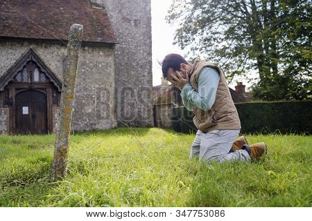 A Young Man Grieving In The Old Graveyard