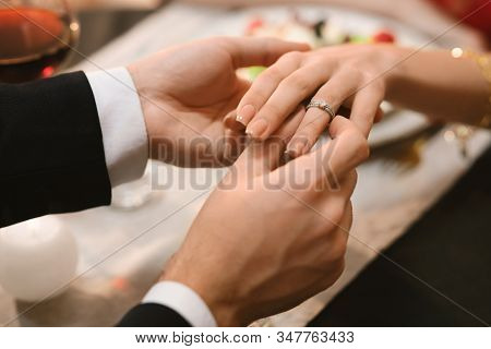 Proposal Date. Unrecognizable Man Putting Engagement Ring On Girlfriends Hand During Romantic Dinner