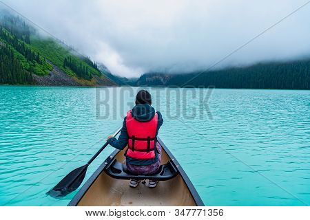 Woman Canoeing In Lake Louise Banff Canada