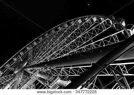 Black And White Picture Of Ferris Wheel In Nighttime With Beautiful Backlight. Bottom View On Famous