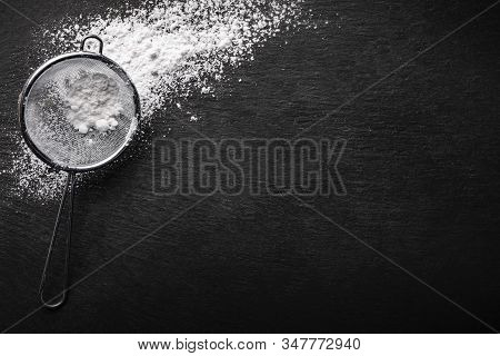 Powdered Sugar Scattered On A Black Stone Countertop With A Sifter For Sifting , Top View.