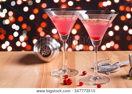 Martini Glasses With Cranberry Cocktail And Barmen Tools On The Wooden Table.