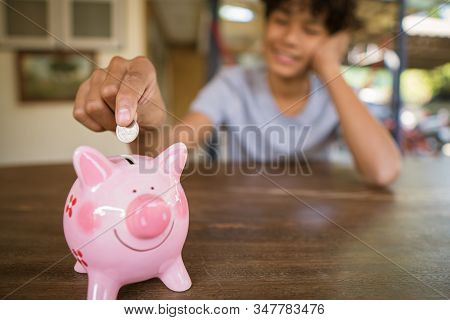 Asian Boy Putting Money In Piggy Bank To Save For The Future