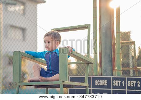 Cute Young Mixed Race Boy  Sitting On A Tennis Umpire Chair