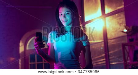 Smiling, Looking Forward. Cinematic Portrait Of Stylish Woman In Neon Lighted Interior. Toned Like C