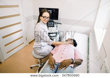 Young Smiling Woman Doctor In Diagnostic Center Making Ultrasound Thyroid Gland Test To Female Afric