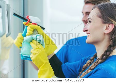 Commercial cleaners cleaning an office window wearing gloves