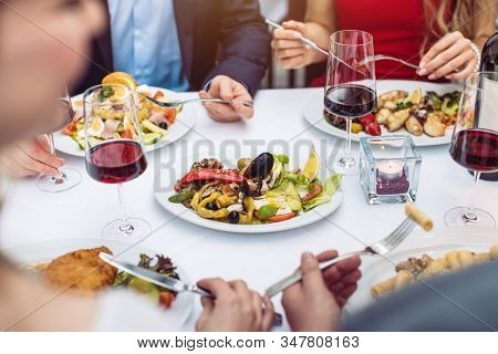 Four friends eating Italian food in fancy restaurant, close-up on the dishes