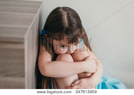 Sad Little Girl Crying At Her Bedroom Holding Her Knees