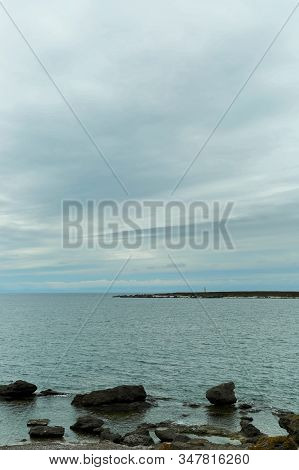 Ocean With Rocky Shore And Lighthouse With A Cloudy Sky.