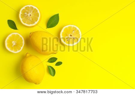 Creative Background With Fresh Lemons And Green Leaves On Bright Yellow Background. Top View Flat La