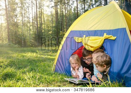 Four children of different age reading a book lying together in tent camping in a summer forest during summer holidays