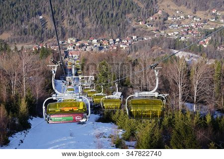 Szczyrk, Poland 15.01.2020: Ropeway Empty Chairlift In The Mountains With A Yellow Cover Cabin Or Ca
