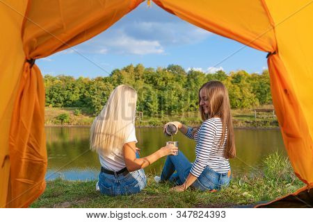 Camping On Lake Shore At Sunset, View From Inside Camping Tent. Two Beautiful Girls Enjoy Nature And
