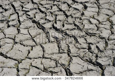 Part Of A Huge Area Dried Land Suffering From Drought - In Cracks. Dry Water Reservoir. Natural Drou