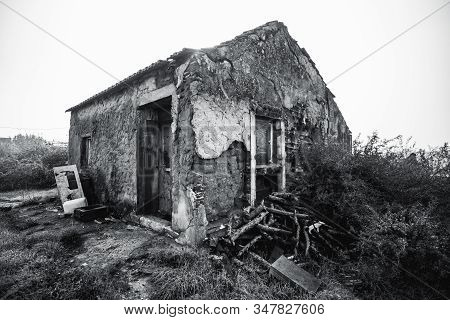 A Wide-angle Black And White Shot Of A Desolate Stone House With Rough Flaked Walls Covered With Cem