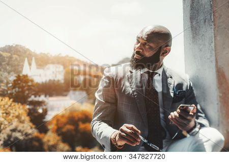 A Handsome Mature Bearded African Man In A Formal Suit With A Cellphone And Eyeglasses In His Hands;
