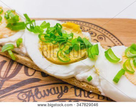 Breakfast Open Sandwich With Soft Cream Cheese Ricotta, Eggs, Onion On A Rustic Wooden Board. Crispb