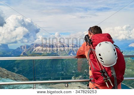 Man Tourist With Trekking Poles And Climbing Helmet On Its Backpack Looking Towards Sella Group In D