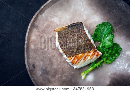 Gourmet fried European skrei cod fish filet with rapini broccoli rabe as top view on a modern design plate with copy space left