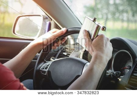 Drunk Driver Is Driving A Car On The Road And Drinking A Strong Alcohol From A Flask Close Up.