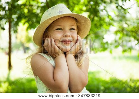 Portrait Of Cute Child Girl Model In Hat Smiling In Park Or Outdoor. Happy Childhood, Summer Holiday