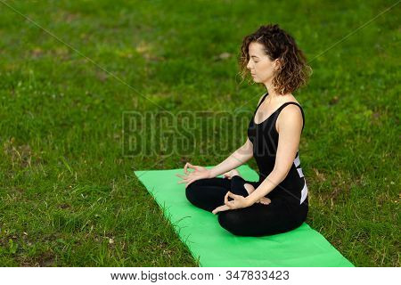 Young Woman In Park Practicing Yoga. Sukhasna Pose.