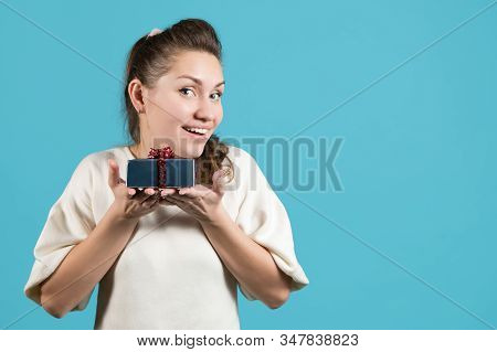 Young Woman Holds A Small Gift On Her Palms Close To Herself And Smiles Brightly. Blue Background, C
