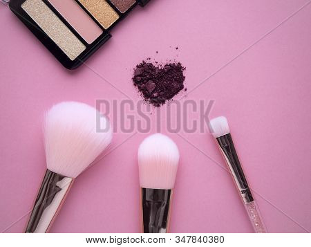 Cosmetic Nylon Makeup Brushes On Pink Background With Crushed Plum Shimmer Eyeshadows In Heart Shape