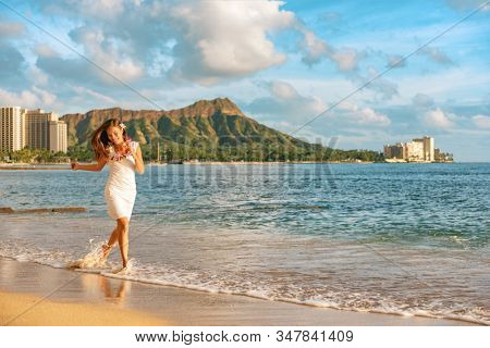 Hawaii vacation woman relaxing on Waikiki beach running carefree enjoying holidays in Honolulu City wearing flower lei for hula dancer luau party at sunset.