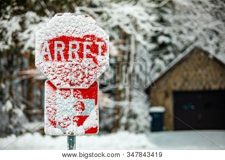 A Selective Focus Shot Of A French Canadian Traffic Control Sign Saying Stop, Covered With Snow And