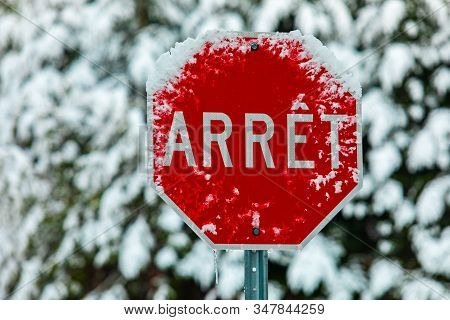 A Close Up Selective Focus Shot Of A Traffic Sign Saying Arret, French For Stop, Seen On A Street In