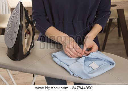 Female Hands Fold A Ironed T-shirt Lying On An Ironing Board. The Iron Stands On A Foot On An Ironin