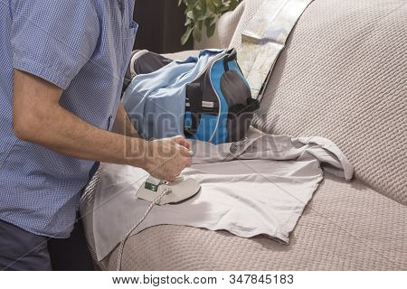Ironing Clothes On Vacation. The Man Irons Clothes With A Tourist Iron. The T-shirt And Travel Bag L