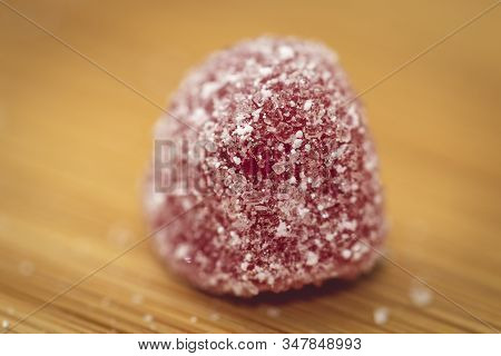 A Macro Portrait Of A Sugar Sprinkled Red Piece Of Candy On A Wooden Table. There Is Suger Sprinkled