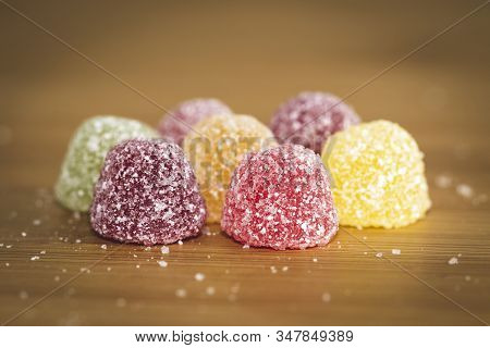 A Close Up Portrait Of Soms Colorful Sugar Sprinkled Pieces Of Cany. The Sweets Are Placed On A Wood