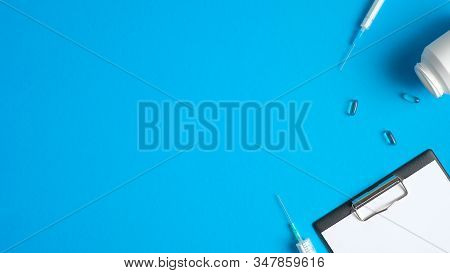 Frame Border Of Medical Tools And Equipment On Blue Background. Top View Doctor Table With Syringes,