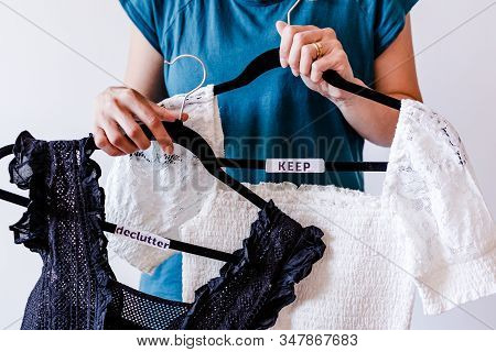 Tidying Up And Decluttering Conceptual Still-life, Woman Holding Clothes Hangers With Black And Whit