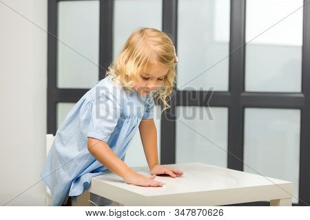 Cute Little Girl Cleaning The Table In The Kitchen. She Helps Mom In Cleaning Up The House. The Conc