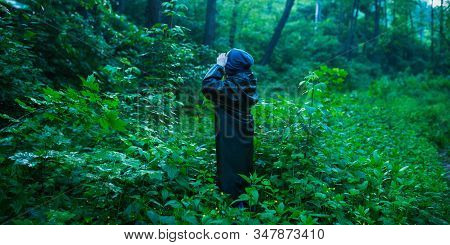 Man In Rain Coat On Background Of Wet Forest. Green Summer Nature. Feel Loneliness. Man Travel In Ra