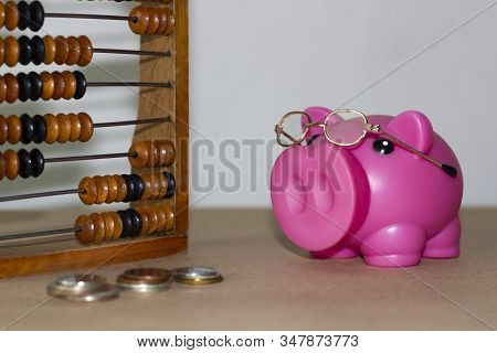 Pink Piggy Bank With Glasses On A Light Background Next To Abacus And Money. Financial Concept.