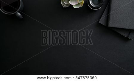Overhead Shot Of Dark Modern Workplace With Copy Space, Camera Lens, Office Supplies And Decorations