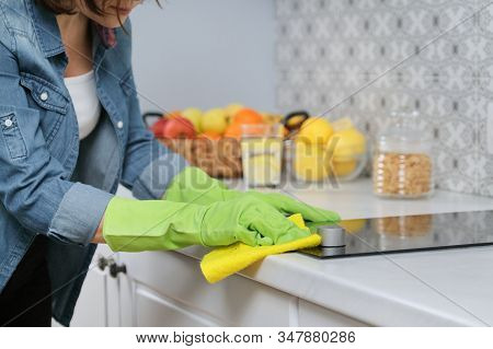 Close-up Of Cleaning Kitchen, Woman Hands In Gloves Washing And Cleaning Electric Hob In Kitchen Wit