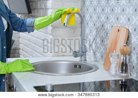 Woman In Gloves With Rag Cleaning House In Kitchen. Female Washing Cleaning Polishing Kitchen Sink A