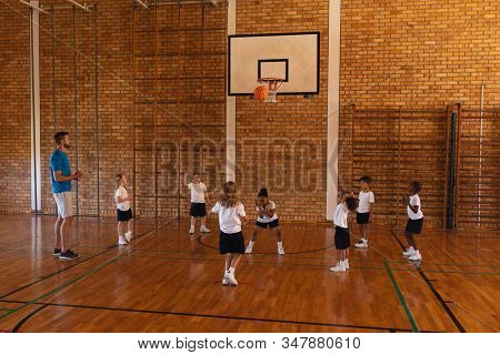 Basketball coach teaching to schoolkids at basketball court in school