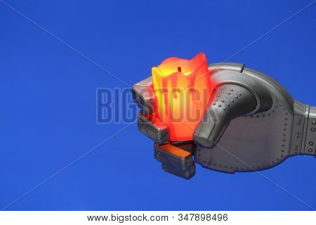 Robot Hand With A Candle. Mourning, Grief, Sadness. The Sad Robot. The Candle Is Off. Robot Hand Hol