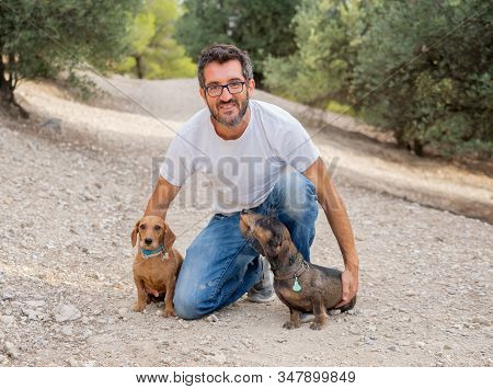 Happy Owner Man With Two Old Sweet Dachshund Dogs Having Fun In The Park. In Animal Lovers, Companio